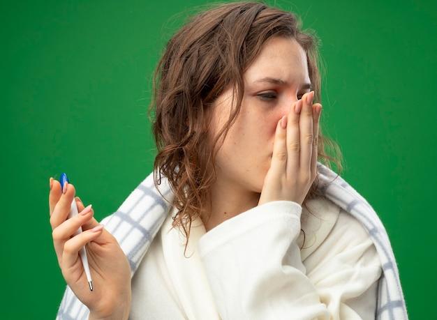온도계를 들고 격자 무늬에 싸여 흰 가운을 입은 약한 어린 아픈 소녀가 녹색에 고립 된 손으로 입을 덮었습니다.