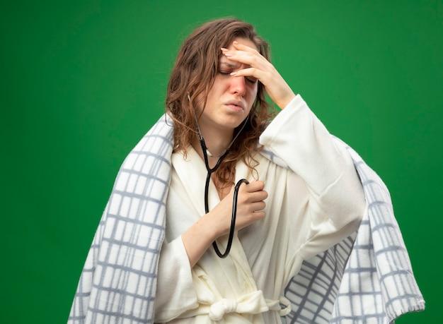 聴診器で自分の心拍を聞いて、緑で隔離された額に手を置く格子縞に包まれた白いローブを着ている弱い若い病気の女の子