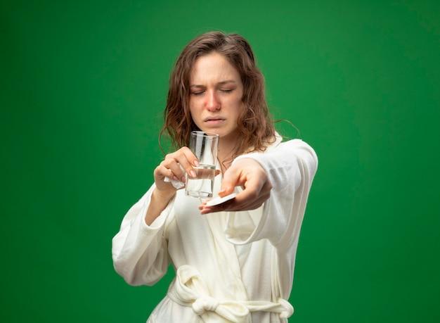 目を閉じて、水のガラスを保持し、緑で隔離の丸薬を保持している白いローブを着ている弱い若い病気の女の子