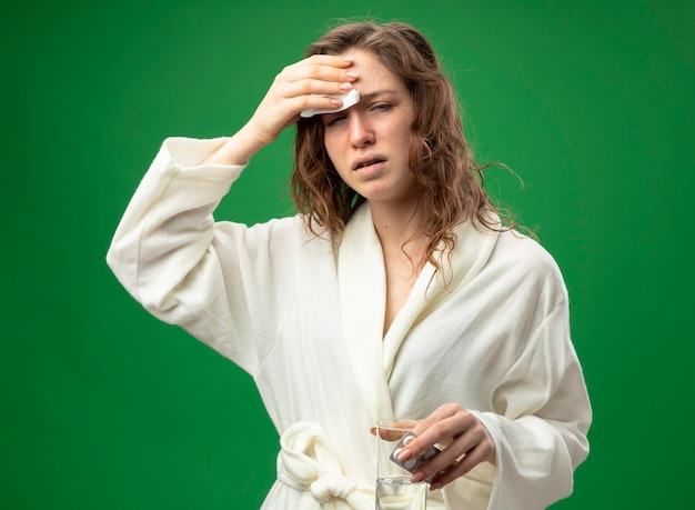 緑に分離されたナプキンで額を拭く水のガラスを保持している白いローブを着て目を閉じて弱い若い病気の女の子