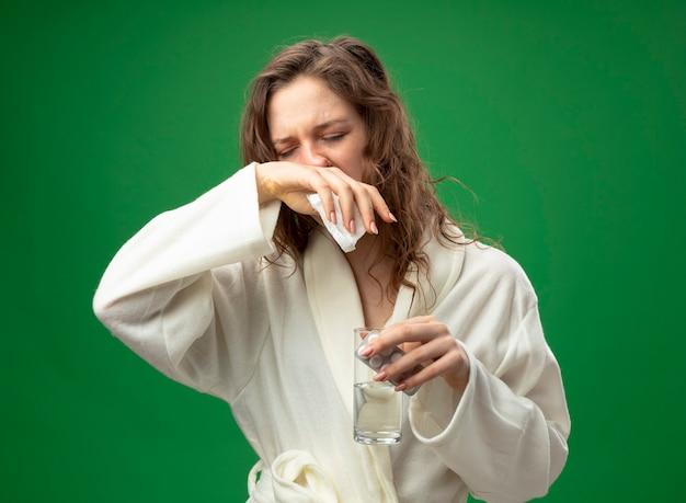 Debole giovane ragazza malata con gli occhi chiusi che indossa una veste bianca tenendo un bicchiere di acqua con le pillole e asciugandosi il naso con la mano isolata su verde
