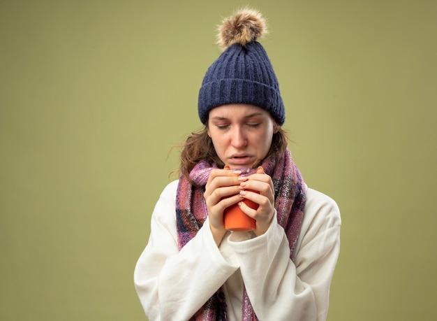 Debole giovane ragazza malata con gli occhi chiusi che indossa una veste bianca e cappello invernale con sciarpa che tiene tazza di tè isolato su verde oliva