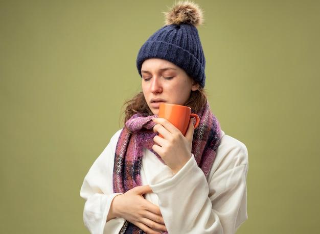 Debole giovane ragazza malata con gli occhi chiusi che indossa una veste bianca e cappello invernale con sciarpa che tiene tazza di tè mettendo la mano sullo stomaco isolato su verde oliva