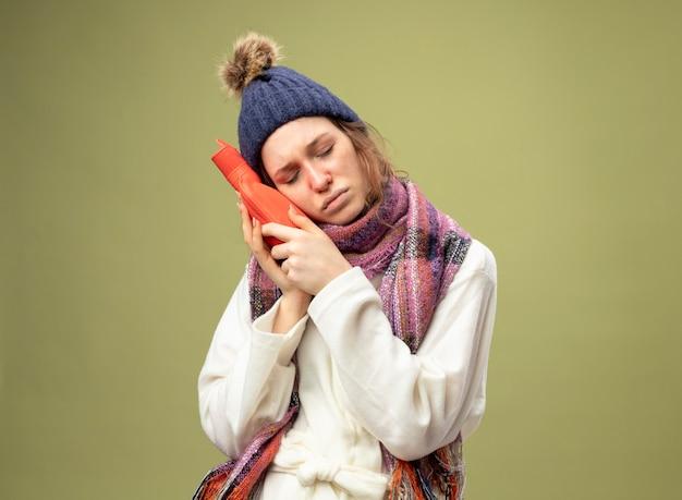 Debole giovane ragazza malata con gli occhi chiusi che indossa una tunica bianca e cappello invernale con sciarpa che tiene la borsa dell'acqua calda sulla guancia isolata su verde oliva