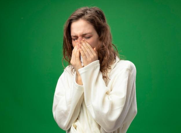 緑に分離されたナプキンで鼻を拭く白いローブを着て目を閉じて弱い若い病気の女の子