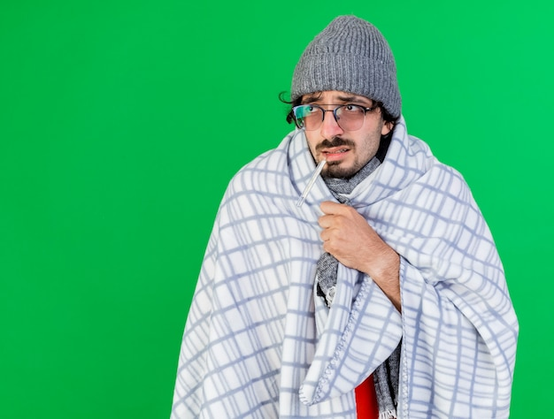 Слабый молодой больной человек в очках, зимней шапке и шарфе, завернутый в плед, держит во рту термометр и смотрит на бок, хватаясь за плед, изолированный на зеленой стене