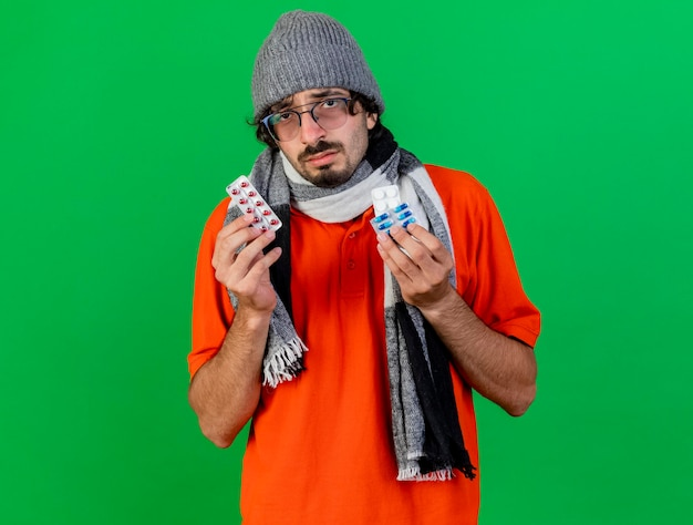 Weak young ill man wearing glasses winter hat and scarf holding medical pills looking at front isolated on green wall with copy space