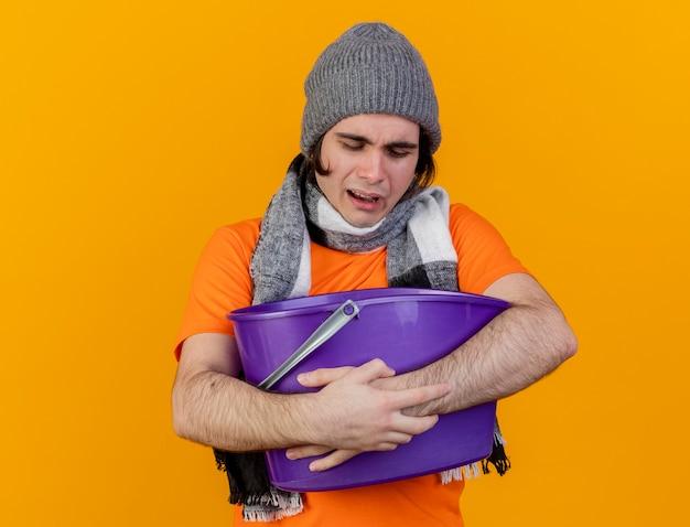 オレンジ色の背景で隔離のプラスチック製のバケツを保持している吐き気を持っているスカーフと冬の帽子をかぶって弱い若い病気の男