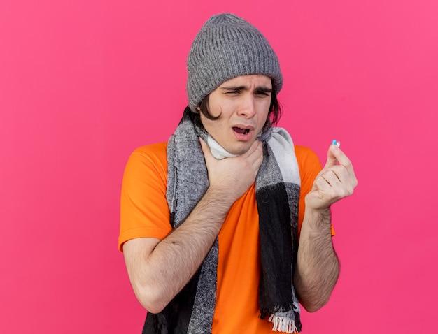 Debole giovane uomo malato che indossa un cappello invernale con sciarpa che tiene la pillola e ha afferrato la gola dolorante isolata sul colore rosa