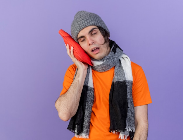 Weak young ill man wearing winter hat with scarf putting hot water bag on cheek isolated on purple