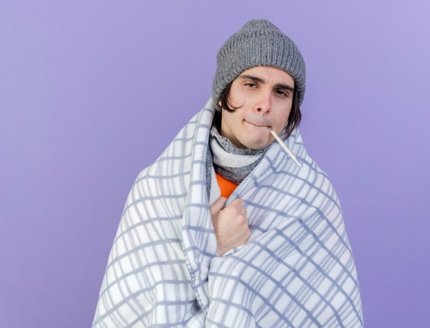 Weak young ill man wearing winter hat with scarf wrapped in plaid holding thermometer in mouth isolated on purple background