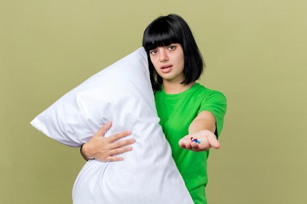 Debole giovane donna malata che tiene il cuscino guardando la parte anteriore che allunga le capsule mediche verso la parte anteriore isolata sulla parete verde oliva