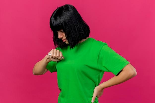 Debole giovane donna malata in piedi in vista di profilo tenendo la mano sulla vita tenendo il tovagliolo guardando in basso isolato sulla parete rosa con spazio di copia