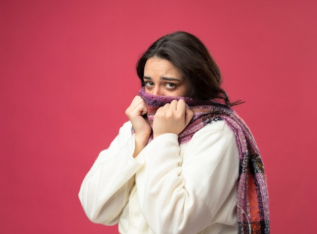 분홍색 벽에 고립 된 스카프에 손을 유지하는 스카프로 입을 덮고있는 프로필보기에 서있는 가운과 스카프를 착용하는 약한 젊은 아픈 여자