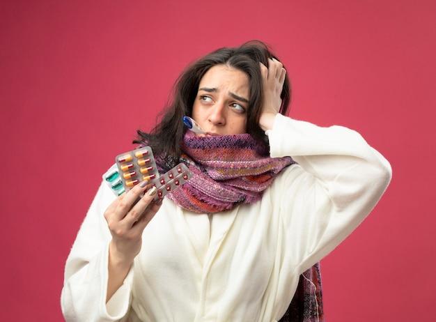 Debole giovane donna malata che indossa accappatoio e sciarpa che tiene confezioni di capsule mediche con termometro in bocca guardando il lato tenendo la mano sulla testa isolata sul muro rosa