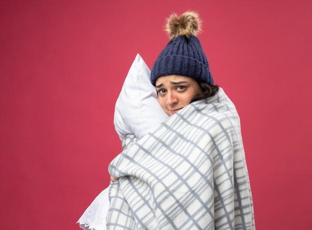 가운 겨울 모자와 스카프를 착용하는 약한 젊은 아픈 여자는 분홍색 벽에 고립 된 전면을보고 포옹 베개 프로필보기에 격자 무늬 서에 싸여