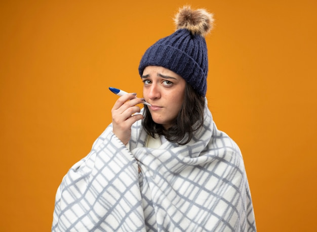 オレンジ色の壁に隔離された正面を見て温度計を口に入れて格子縞に包まれたローブの冬の帽子を身に着けている弱い若い病気の女性
