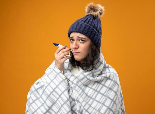Debole giovane donna malata che indossa un abito invernale cappello avvolto in plaid che mette il termometro in bocca guardando la parte anteriore isolata sulla parete arancione