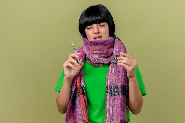 주사기와 앰플을 들고 스카프를 착용하는 약한 젊은 아픈 여자는 복사 공간이 올리브 녹색 벽에 고립 된 전면을보고