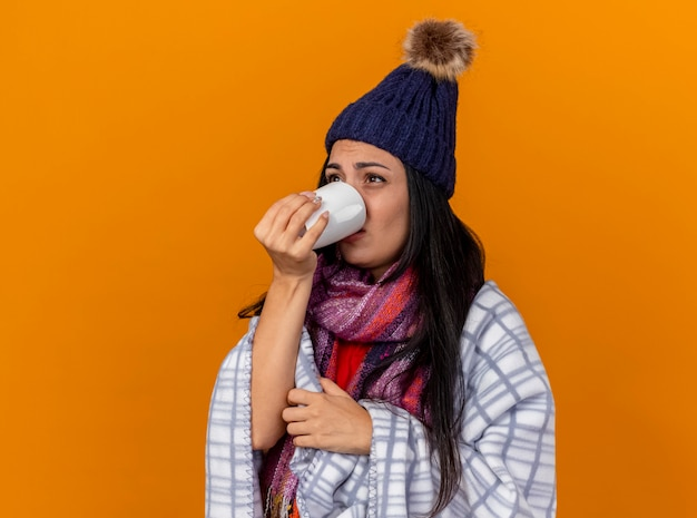 Слабая молодая больная женщина в зимней шапке и шарфе, завернутом в плед, стоит в профиль и пьет чашку чая, глядя прямо на оранжевую стену