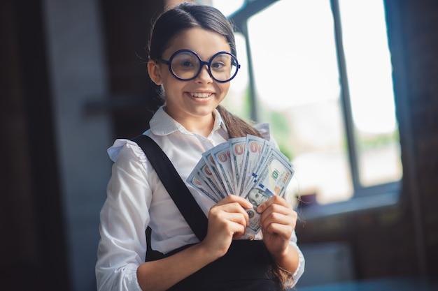 Состоятельный. девушка в белой рубашке держит доллары и выглядит довольной