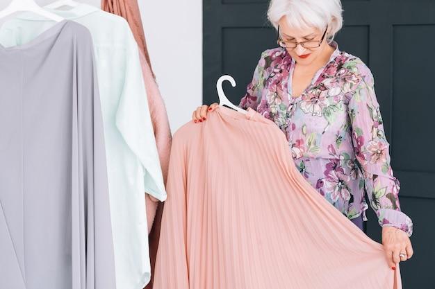 裕福なシニアライフスタイル。ファッション洋服の買い物。エレガントな服を着ようとしている自信のある年配の女性。