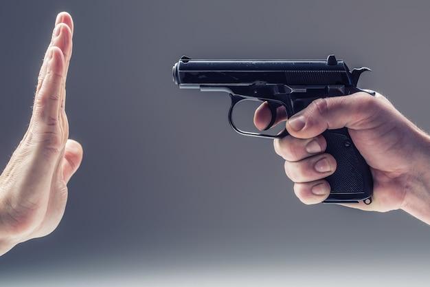 Оружейный пистолет. мужская рука держит пистолет. вторая рука защищается.
