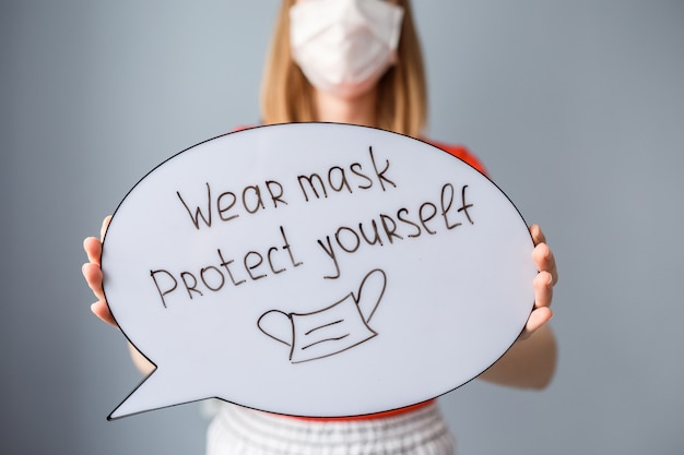 マスクを着用-女性の手の吹き出しの碑文を保護してください。女性はcovid 19の流行中にマスクを着用しています。