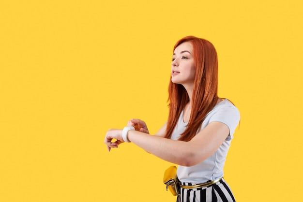 Носимая техника. милая молодая женщина нажимает на экран своих умных часов, стоя на желтом фоне