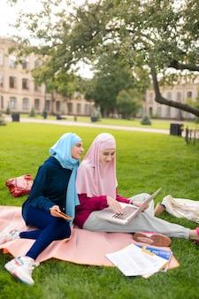 В ярких хиджабах. привлекательные студенты в ярких хиджабах чувствуют себя счастливыми, занимаясь вместе на улице