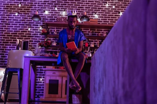 В женском наряде. усталый мужчина с похмелья сидит на столе и планирует процедуру уборки своей разрушенной комнаты