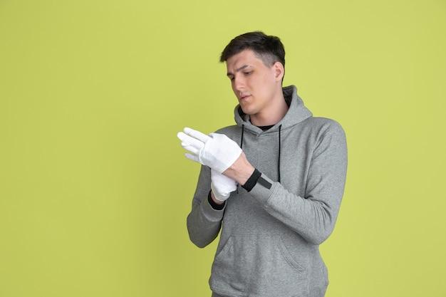 手袋を着用します。黄色のスタジオの壁に分離された白人男性の肖像画。