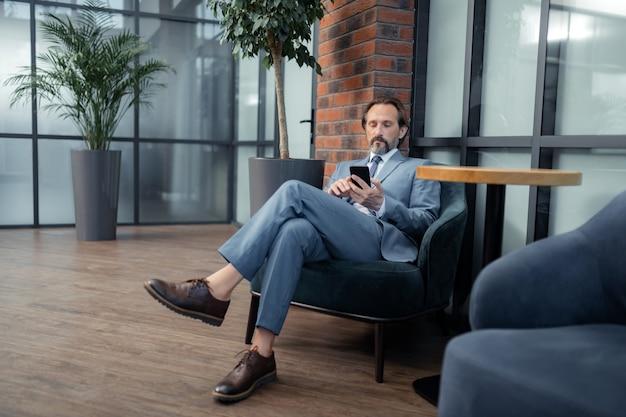 灰色のスーツを着ています。彼の電話で電子メールを読んで灰色のスーツを着ているひげを生やした成熟したビジネスマン