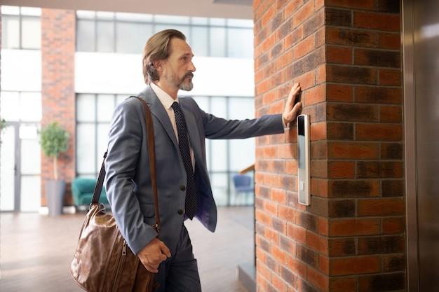 В сером костюме. седовласый бизнесмен в сером костюме в ожидании лифта в бизнес-центре