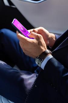 Ношение ручных часов. бизнесмен носить ручные часы, держа смартфон во время чтения электронной почты