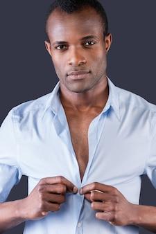 В своей любимой рубашке. красивый молодой темнокожий мужчина одевает рубашку и улыбается в камеру, стоя на сером фоне