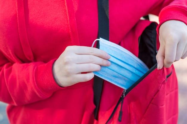공공 장소 개념에서 의료 마스크를 착용합니다. 의료용 마스크를 사용하는 어린 소녀의 클로즈업 사진
