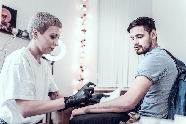 保護手袋を着用してください。特別な消毒スプレーでクライアントの手の表面を準備する正確な短髪の女性マスター