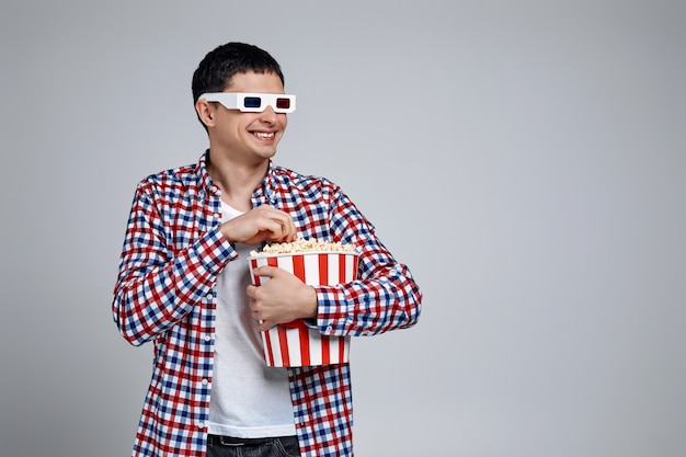 Wearing red-blue 3d glasses and eating popcorn from bucket while watching a movie isolated on gray