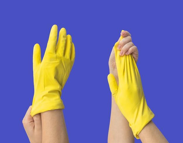 Носить резиновую перчатку, рука с защитной латексной перчаткой на синем изолированном фоне