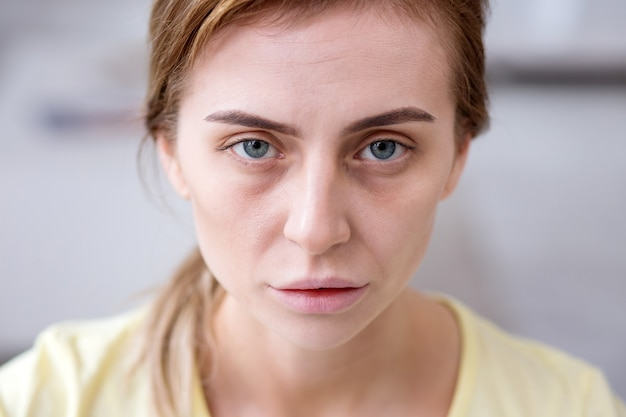 疲れた顔。病気の間にあなたを見ている青白い疲れ果てた女性の肖像画