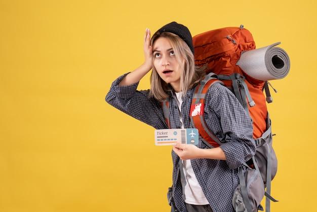 Усталая путешественница женщина с рюкзаком держит ее за голову