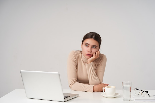 Weary young attractive dark haired lady leaning her chin on raised hand and looking dreamily aside, having long working day and counting time, isolated over white wall