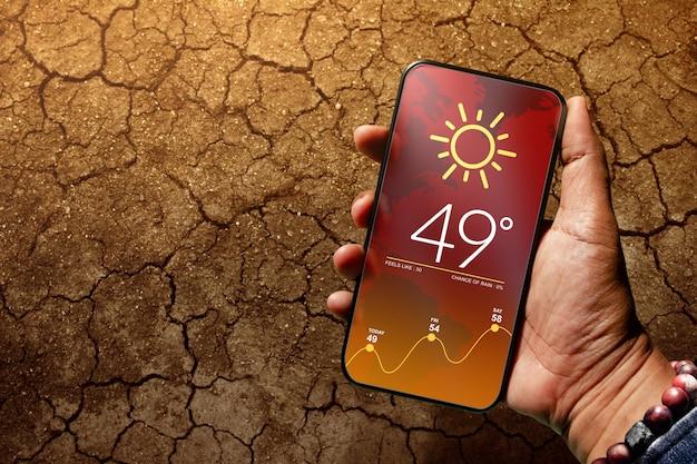 ひびの入った地面にあるスマートフォンの天気アプリ