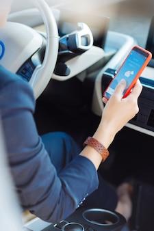 오늘 날씨. 여성 운전자의 손에있는 오늘의 날씨를 보여주는 스마트 폰의 클로즈업