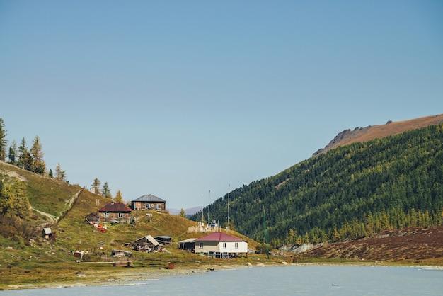 Метеостанция на холме возле горного озера в долине среди высоких лесных гор. живописный осенний пейзаж с горной деревней на берегу озера и горами с хвойным лесом. три дома на холме