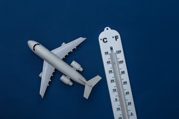 Weather thermometer with  toy plane on classic blue background. color 2020. tiop view