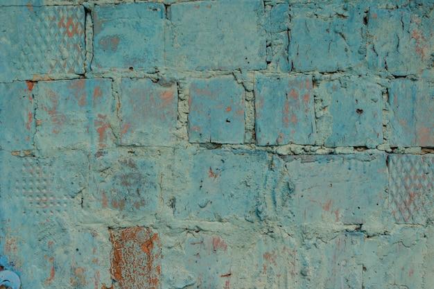 風化した青いステンドグラスの古いレンガの壁の背景。