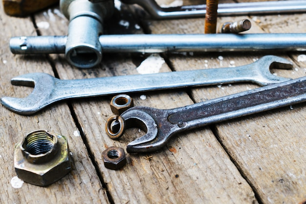 On weathered old wooden surface lie the , oily wrenches.