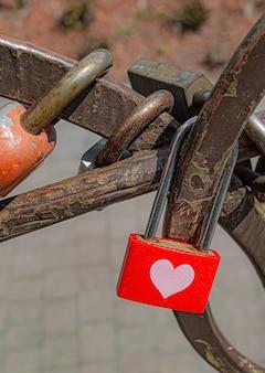 심장이 다른 자물쇠 근처에 매달려 있는 풍화된 빨간색 닫힌 자물쇠.